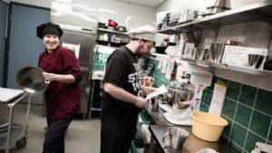 Sampolan asukkaita työskentelemässä keittiössä